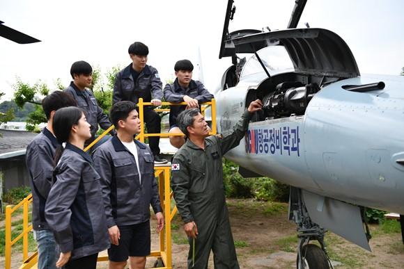 윤대식 학과장(사진 아래 오른쪽)이 실제전투기 FF-5E 모델로 학생들에게 수업을 하고 있다. 사진=서울문화예술대학교 제공