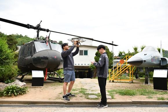 학생들이 UH-1H 헬기와 드론으로 실습을 하고 있다.